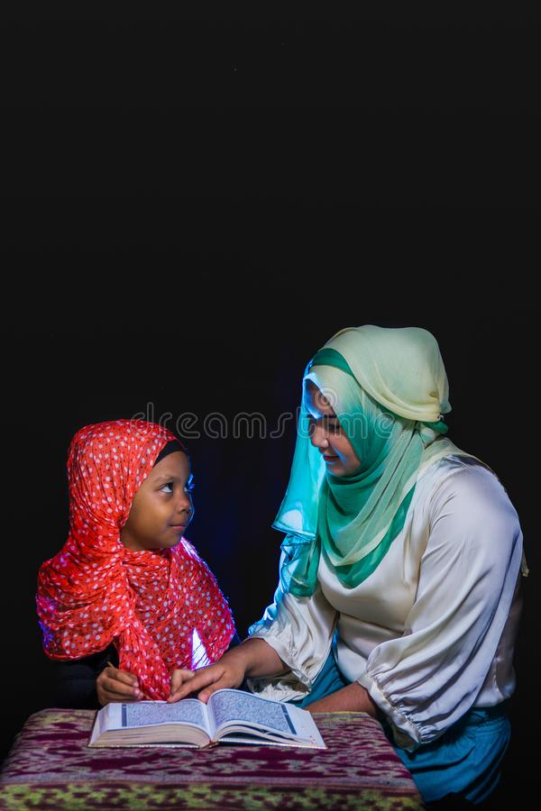 FLORES, INDONESIA-JUNE 25 2014: A hijab sister is teaching her sister who also wears a hijab to read the quran on a table with royalty free stock images