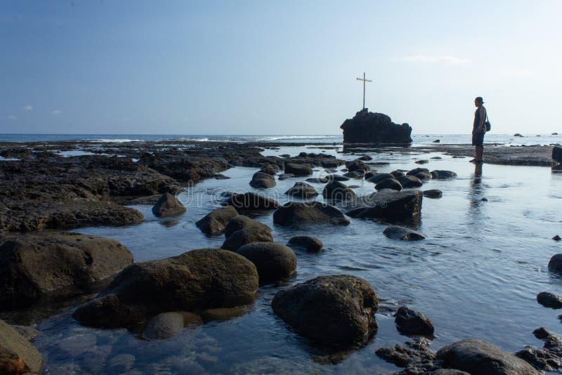 FLORES/INDONESIA-NOVEMBER 16 2012年:Watukrus,弗洛勒斯,印度尼西亚海滩的看法  在海滩和十字架附近的岩石 免版税图库摄影