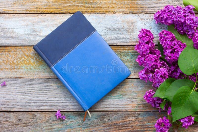 Flores lilás com folhas verdes e o caderno azul fotos de stock royalty free