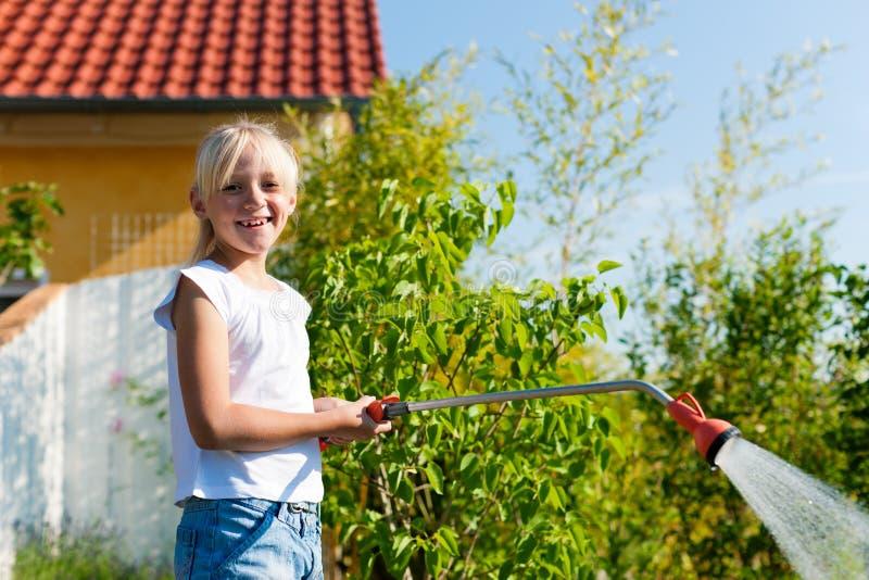 Flores molhando da criança feliz imagem de stock royalty free