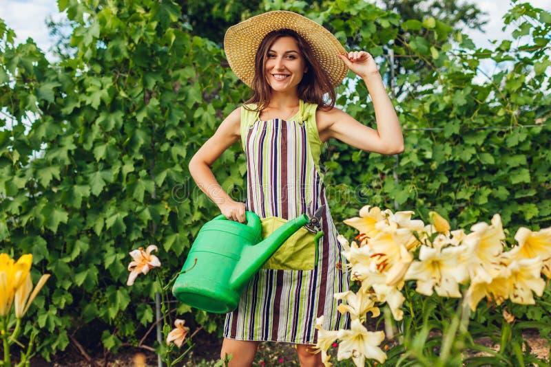 Flores molhando da jovem mulher com a lata molhando no jardim Jardineiro que toma dos lírios Conceito de jardinagem imagens de stock royalty free