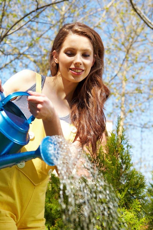 Flores molhando da mulher imagens de stock royalty free