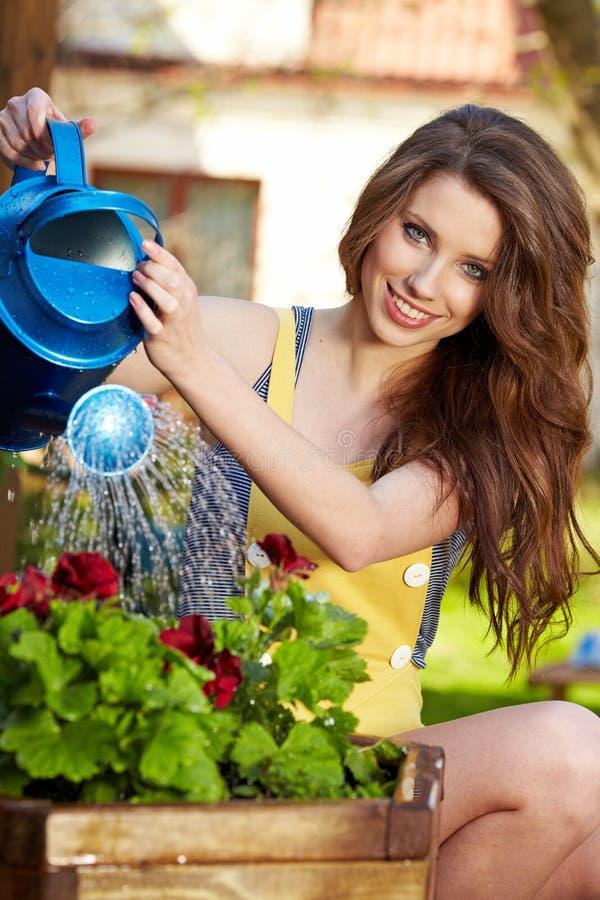Flores molhando da mulher foto de stock