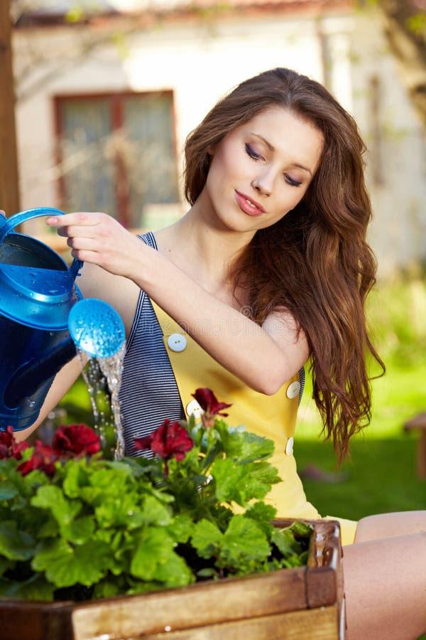 Flores molhando da mulher imagem de stock royalty free