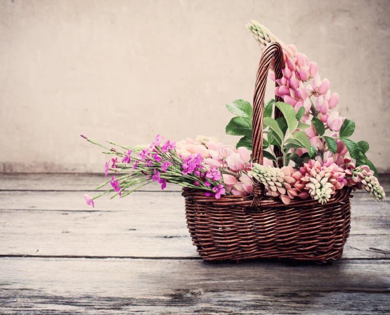Flores na cesta no fundo velho imagem de stock royalty free