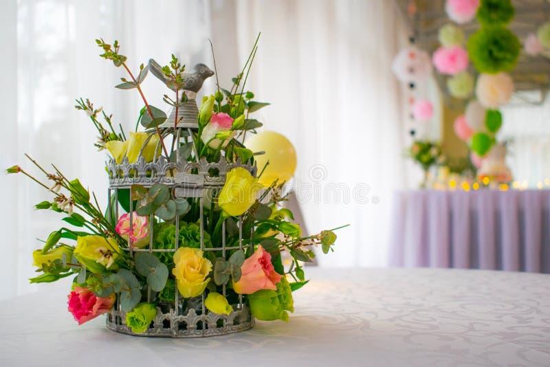 Flores na gaiola de pássaros na decoração branca da tabela imagem de stock royalty free