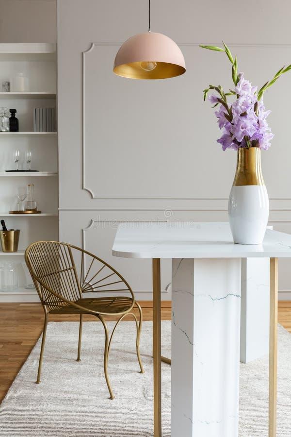 Flores na tabela de mármore branca perto da cadeira do ouro sob a lâmpada cor-de-rosa no interior cinzento da sala de jantar Foto imagem de stock royalty free