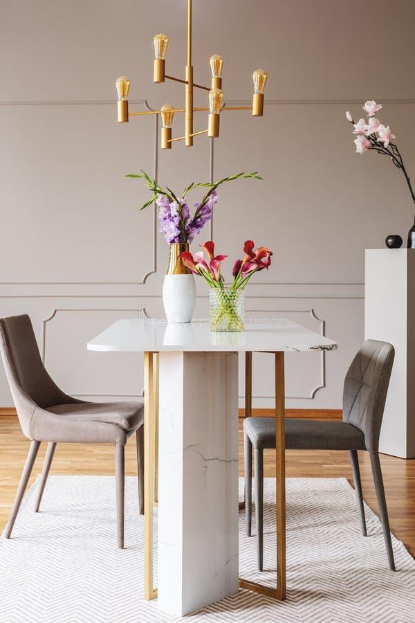 Flores na tabela no interior cinzento da sala de jantar com lâmpada do ouro e cadeiras no tapete Foto real fotos de stock royalty free
