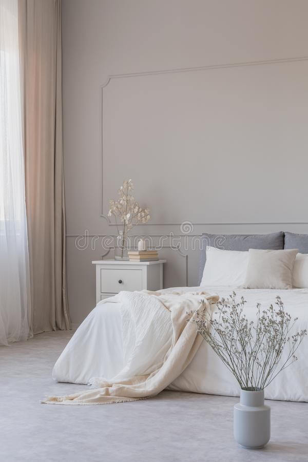 Flores no vaso no assoalho do quarto simples com parede cinzenta e mobília branca, espaço da cópia na parede vazia fotografia de stock