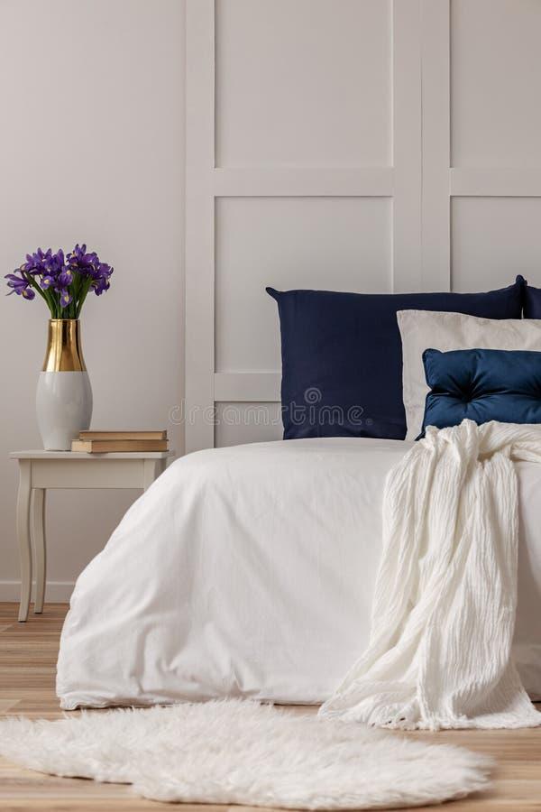 Flores púrpuras en florero y libros en la tabla de madera del nightstand al lado de la cama blanca con las almohadas de los azule imagen de archivo
