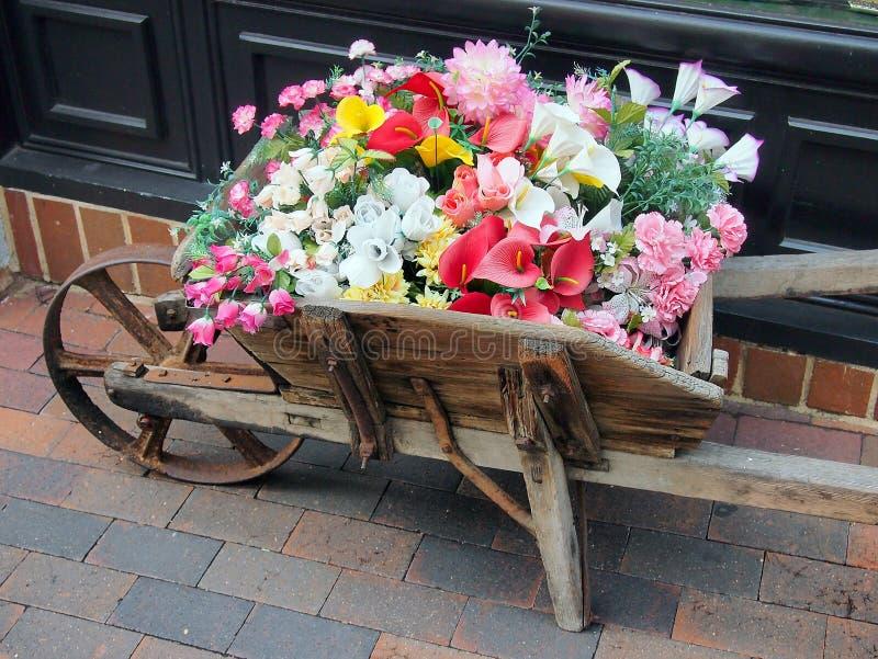 Flores para la venta en carro de madera viejo imagen de archivo libre de regalías