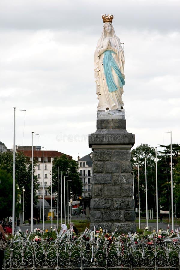 Flores para la Virgen Maria en la ciudad Lourdes del peregrino fotos de archivo