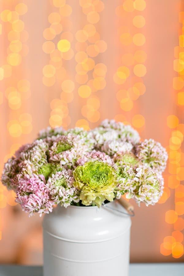 Flores persas cor-de-rosa do botão de ouro O ranúnculo encaracolado da peônia no vintage cinzento metálico pode Vaso com ramalhet imagem de stock royalty free