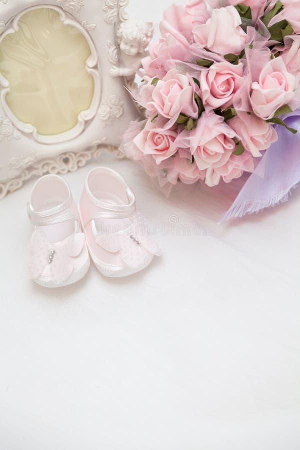 Flores, photoframe y las sandalias de los niños en la cama foto de archivo