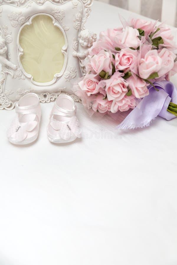 Flores, photoframe y las sandalias de los niños en la cama foto de archivo libre de regalías