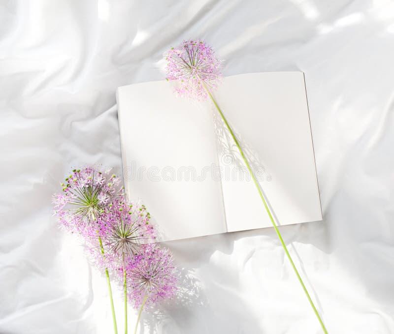 Flores que ficam no livro aberto na cama Bom dia rom?ntico Vista superior imagem de stock
