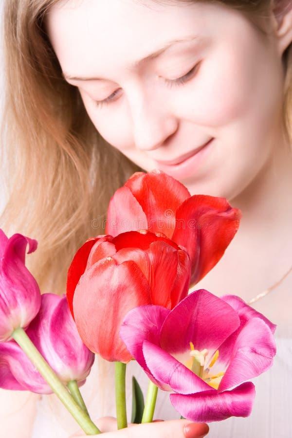 Flores que huelen de la mujer joven fotos de archivo