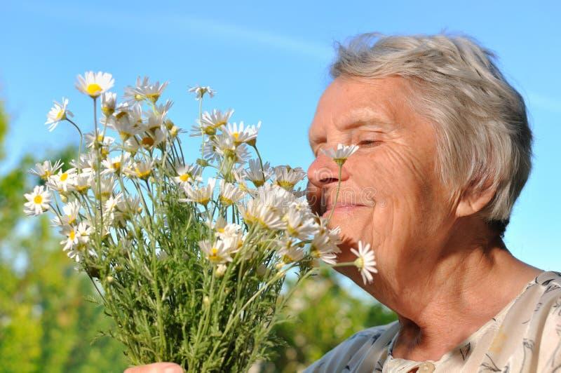 Flores que huelen de la mujer mayor. imágenes de archivo libres de regalías