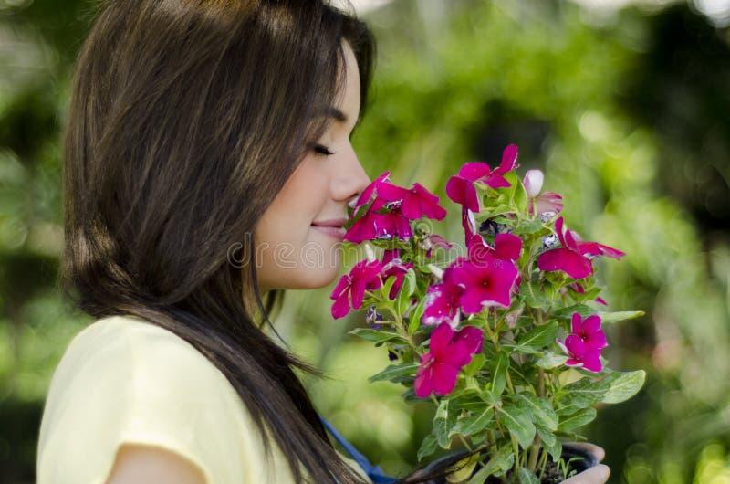 Flores que huelen del jardinero de sexo femenino foto de archivo