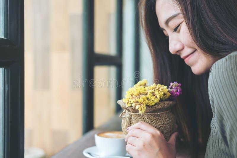 Flores que se sostienen y que huelen de la mujer con la sensación feliz en café de madera del vintage con la taza de café de la f imágenes de archivo libres de regalías