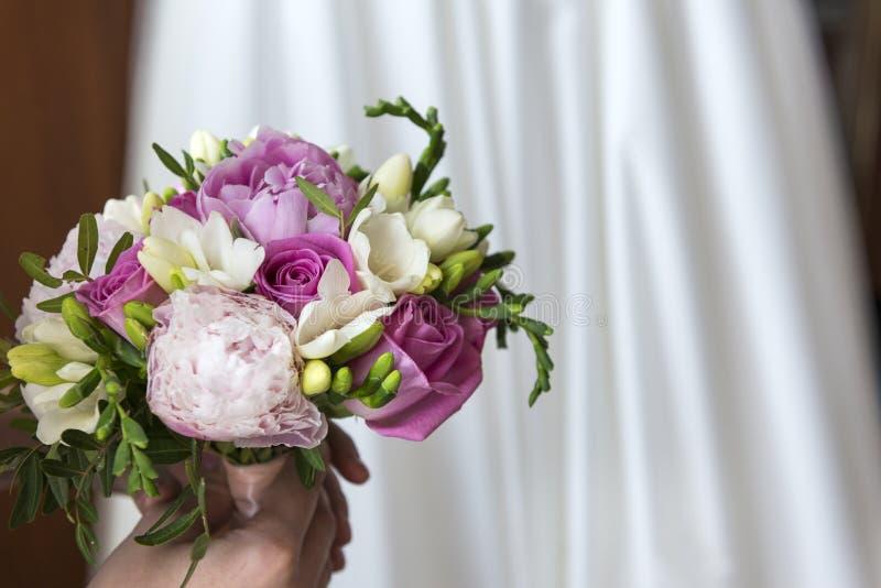 Flores, ramalhete do casamento de rosas cor-de-rosa e peônias no fundo do vestido de casamento branco imagem de stock