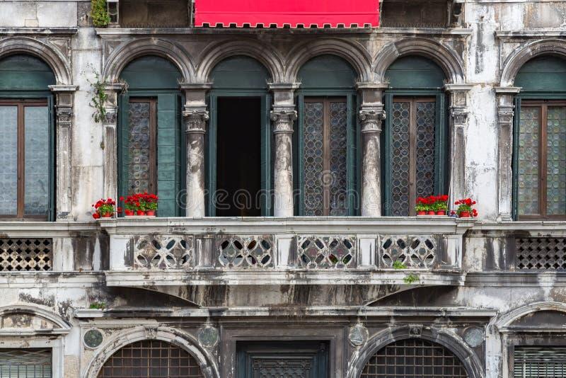Flores rojas en un balcón del vintage en Venecia imágenes de archivo libres de regalías