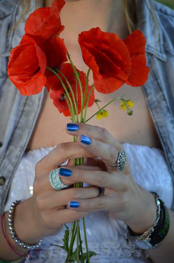 Flores rojas que se consideran femeninas en sus manos fotos de archivo libres de regalías