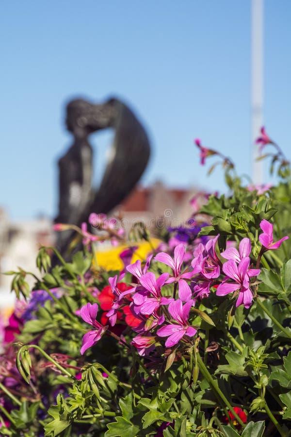 Flores rosadas con las hojas verdes con la estatua de la mujer imágenes de archivo libres de regalías