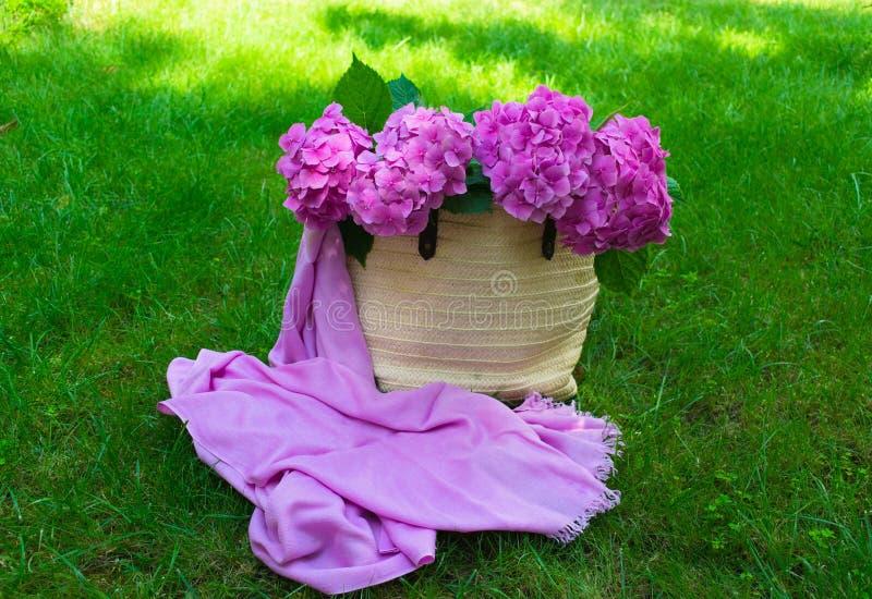 Flores rosadas de la hortensia en un bolso del verano de las mujeres de mimbre en una hierba verde enorme Copie el espacio foto de archivo libre de regalías