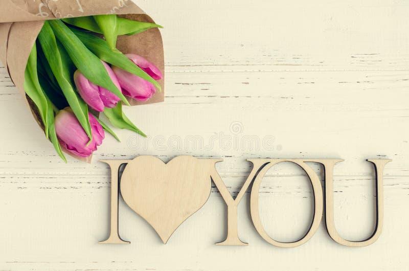 Flores rosadas del tulipán con las palabras de madera TE AMO imagenes de archivo
