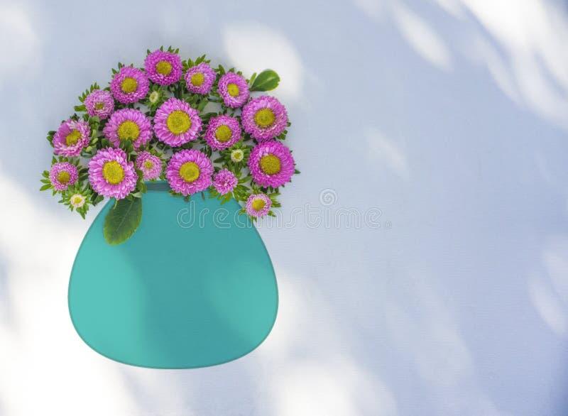 Flores rosadas en un florero de la turquesa, fondo blanco imagen de archivo