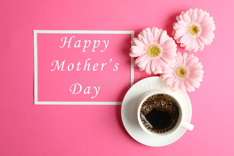 Flores rosadas hermosas del gerbera, taza de café y marco en el fondo del color, visión superior fotos de archivo