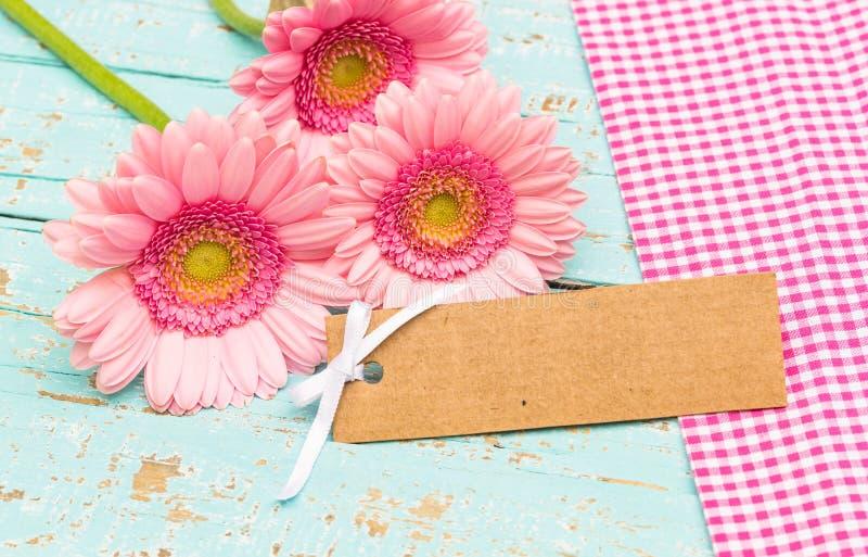 Flores rosadas y carte cadeaux en blanco en fondo de madera azul lamentable fotos de archivo libres de regalías