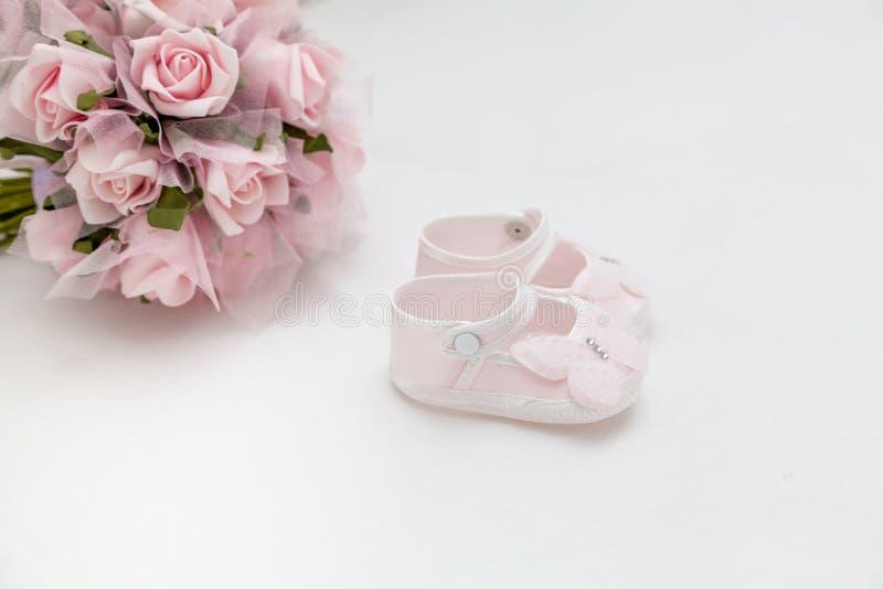 Flores rosadas y las sandalias de los niños en la cama blanca fotos de archivo