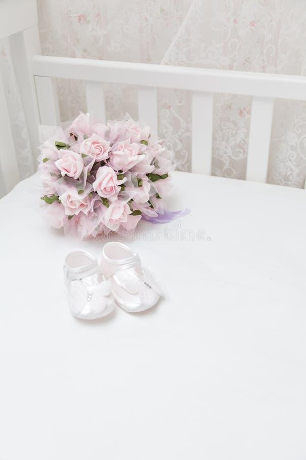 Flores rosadas y las sandalias de los niños en la cama blanca fotografía de archivo libre de regalías