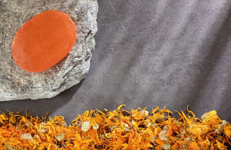 Flores secadas con el jabón hecho a mano en fondo de madera - officinalis del calendula del Calendula fotografía de archivo libre de regalías