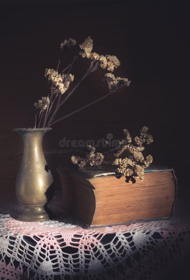 Flores secadas en florero del metal con el libro antiguo imagen de archivo libre de regalías