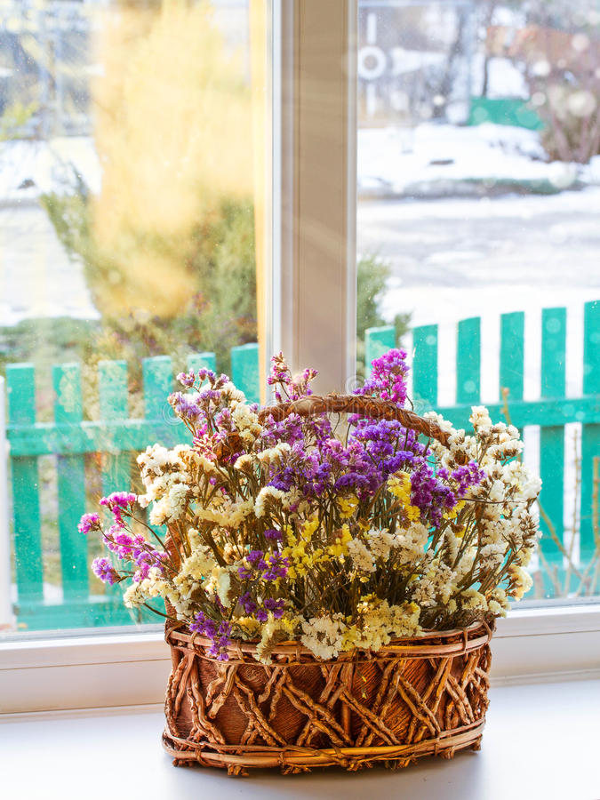 Flores secadas en una cesta en una ventana contra fondo del invierno fotografía de archivo libre de regalías