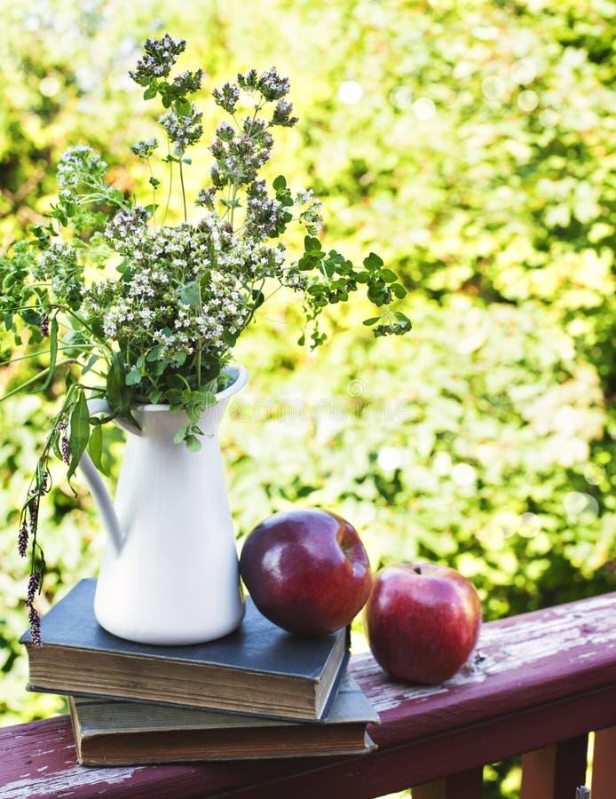 Flores selvagens do verão no vaso de vidro, em livros velhos e em maçãs imagens de stock royalty free