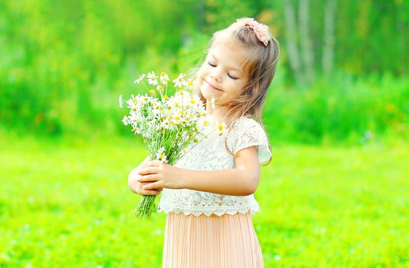 Flores sonrientes felices del ramo de la tenencia del niño de la niña del retrato en sus manos en primavera fotografía de archivo libre de regalías