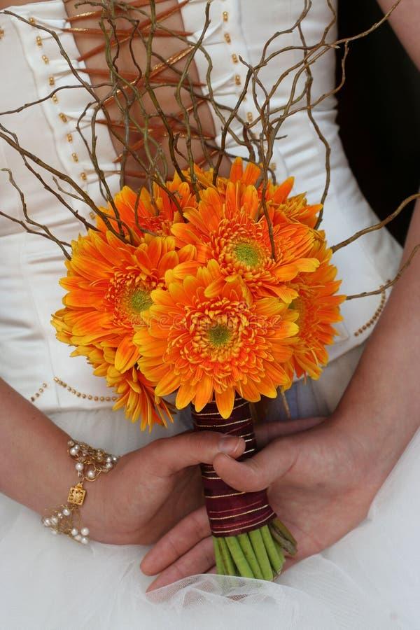 Flores sostenidas por la novia vestida en blanco imagen de archivo libre de regalías