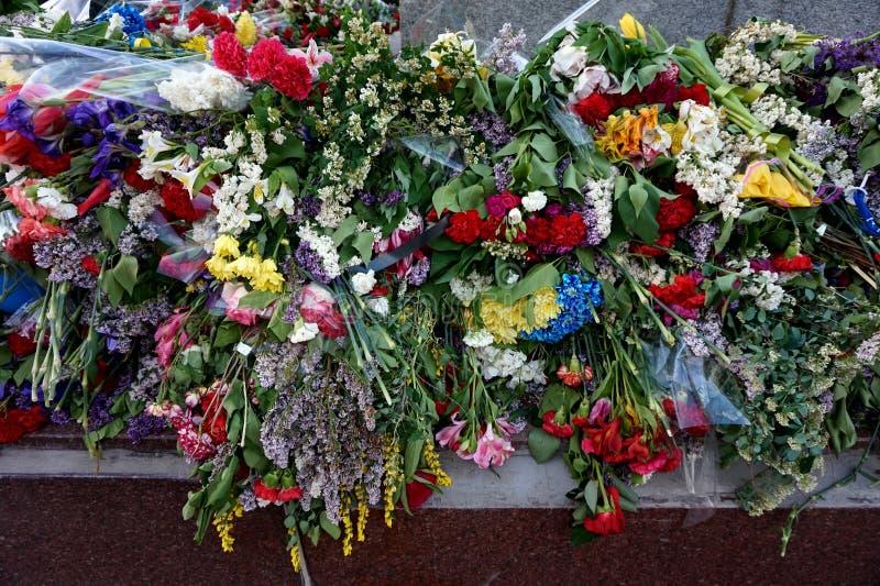 Flores traídas por la gente al ` eterno del fuego del ` ardiente en Victory Day sobre fascismo, el 9 de mayo imágenes de archivo libres de regalías