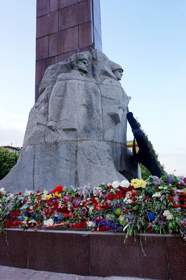 Flores traídas por la gente al monumento de la gloria en Victory Day sobre fascismo, el 9 de mayo fotografía de archivo