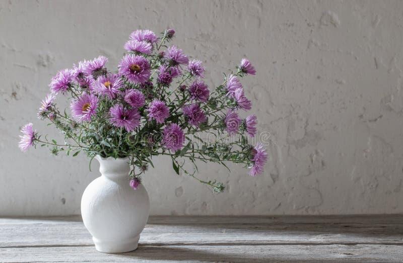 Flores violetas no vaso branco no fundo velho imagens de stock