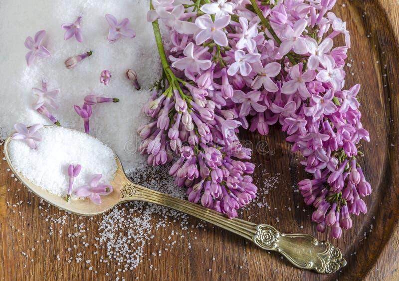 Flores y azúcar de la lila en un tablero de madera fotografía de archivo libre de regalías