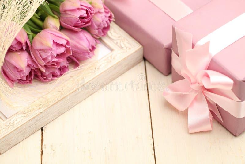 Flores y caja de regalo en fondo de madera imagen de archivo libre de regalías