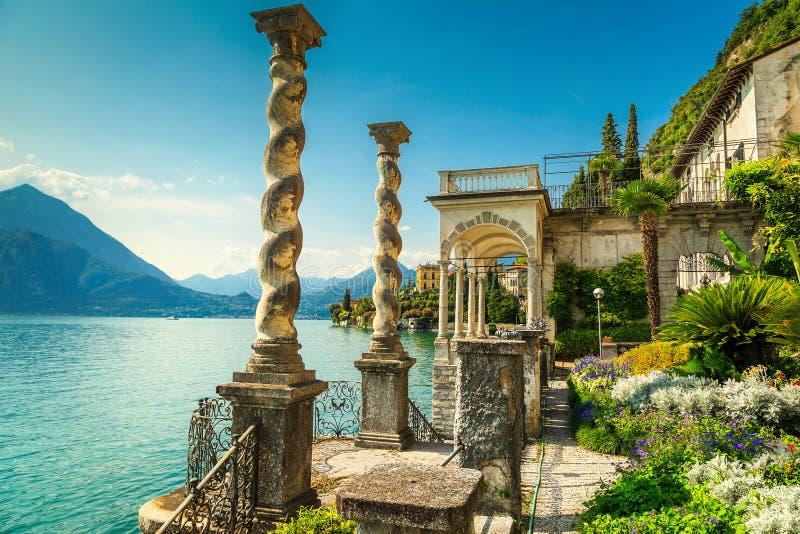 Flores y chalet mediterráneos Monastero en el fondo, lago Como, Varenna fotografía de archivo