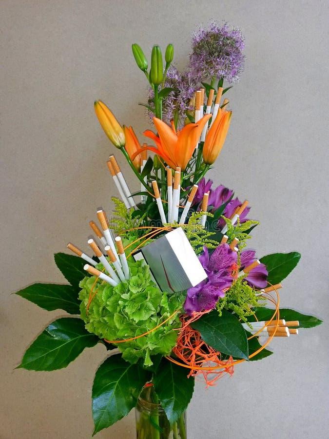 Flores y cigarrillos del ramo en el envase de cristal, con el fondo gris imagen de archivo libre de regalías