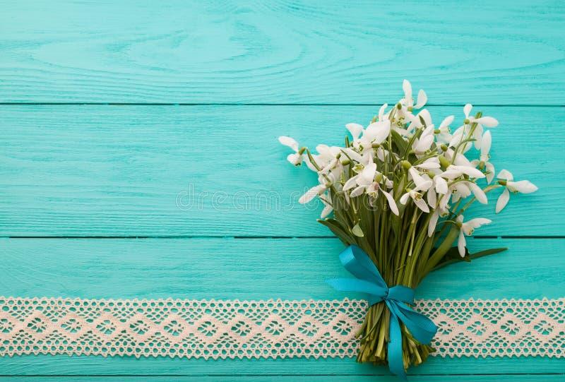 Flores y cinta del cordón en fondo de madera azul imagen de archivo