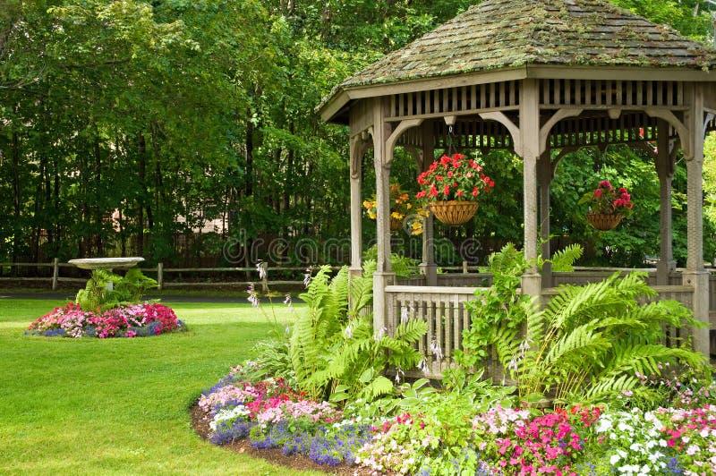 Flores y gazebo en parque imagen de archivo